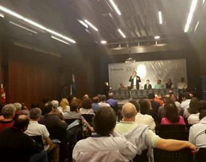 En la imagen vemos decenas de participantes en el congreso y una mesa principal con expositores al fondo