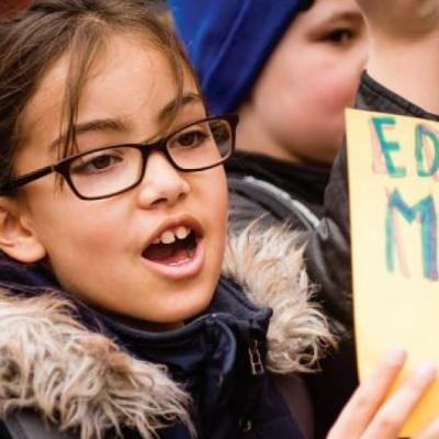 """Una niña sostiene un cartel en una manifestación que indica """"La educación importa"""""""